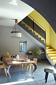 Designer table and wooden chairs in front of anthracite interior staircase