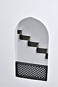 View of black painted runner on narrow staircase through Oriental arched aperture with wooden balustrade
