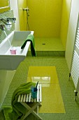 Narrow bathroom with green mosaic tiles and open shower area with lime green cladding