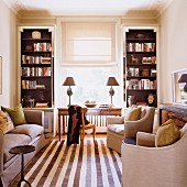 Striped runner rug between a sofa and elegant armchairs in a living room with built in Art-Deco style bookcases next to the window