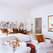 Patterned, upholstered armchairs in front of a bed with a wrought iron frame with a floral design in a simple bedroom
