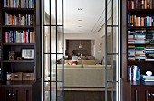 Open sliding glass doors flanked by bookcases and view of pale sofa set in modern living room