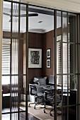 Blick durch halboffene Glas Schiebetüren auf Arbeitsplatz mit zwei Büro Drehstühlen am Fenster und dunkelbraune Stofftapete an Wand