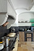 Vintage kitchen counter with worksurface and splashback in black stone below masonry extractor hood in rustic kitchen with arched niche in wall