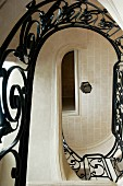 View up through oval stairwell with wrought iron balustrade in grand house