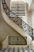 Curved staircase with wrought iron balustrade below window with closed blind in foyer with stone tiles on walls