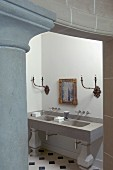 Doorway next to classical stone column with view of modern washstand below antique sconce lamps