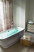 Free-standing bathtub in front of window with closed louver blinds; toiletries on modern side table