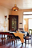 Antique chairs and metal stools around a dining table covered with an cowhide rug; china hutch in front of a wood paneled wall