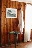Three legged stool in front of a wood paneled wall with a photograph and towel hanging from a hook