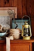 Öllampe, Schnurknäuel und Meeresdeko auf Holzkommode