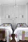 Metal beds with patchwork quilts in front of a wood wall painted white with a shelf