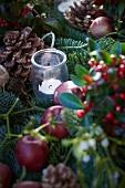 Christmas arrangement of fir branches, wintergreen, bay, apples, mistletoe, pine cones and tealight holder