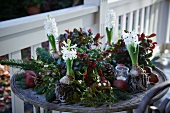 Christmas arrangement of fir branches, wintergreen, bay, apples, mistletoe, hyacinths, pine cones and tealight holder on terrace