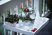 Christmas decorations on terrace: arrangement on cake stand, tealight holders, potted Gaultheria