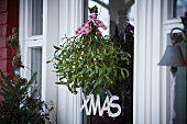 Branches of mistletoe hanging in front of front door as Christmas decoration