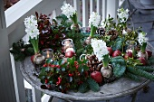 Christmas arrangement of fir branches, wintergreen, bay, apples, mistletoe, hyacinths, pine cones and tealight holders on terrace table