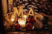Christmas arrangement with the letters XMAS, tealight holders, fairy lights and red apples