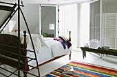 Moderner, offener Schlafbereich mit antikem Bett gegenüber offener Terrassen-Flügeltür und teilweise sichtbarer Teppichläufer mit bunten Streifen