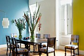 Chairs covered in fabric with modern, graphic patterns and antique table in spacious dining room with one wall painted blue and one yellow