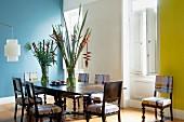 Mit grafischen Mustern modern bespannte Stühle und Antiktisch in grosszügigem Esszimmer mit blau und gelb getönter Wand