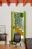 Slatted wooden chairs in front of green-painted exterior door