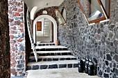 Überdachter Eingangsbereich aus Naturstein eines mediterranen Wohnhauses mit Treppenaufgang unter Rundbogen