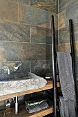 Rustic stone wash basin on wooden counter with ladder-like towel rack leaning on wall in corner of bathroom with marbled stone tiles