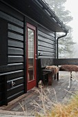 Autumn mist over wooden house with terrace and wooden corner bench