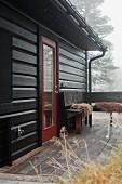 Herbstnebel über Holzhaus mit Terrasse und Holzbank übereck