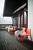 Sheepskins on red plastic chairs on wooden chalet balcony