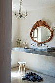 Antique oval mirror above narrow concrete washstand, delicate stool and crystal chandelier in Provençal bathroom