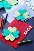 Einladungskarten mit Origami-Kleeblatt dekoriert