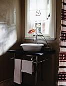 Vase mit Anthurien auf kleinen Waschtisch mit Metallgestell und weisser Waschschüssel vor Fenster in schlichtem Ambiente