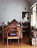 Antique wooden chair in front of a carved, wooden sleigh bed and modern portrait painting on the wall in a no frills room