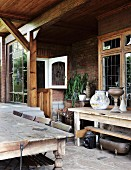 Rustic wooden table with chairs on a covered terrace in front of a country home with a brick facade and Art Nouveau lead glass windows