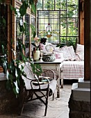 Cozy corner of a country home veranda - rattan chair and rustic wooden table with peeling paint next to a day bed along a stained glass wall