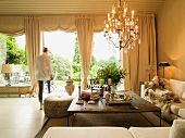 Elegant yet comfortable seating area with expansive corner sofa and chandelier; view of garden through curtains and pelmets of draped Roman blinds