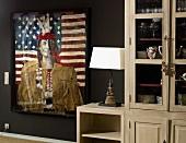 Indianer vor amerikanischer Flagge als moderne Malerei mit Collage-Elementen neben einer Geschirrvitrine im Landhausstil