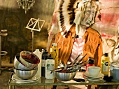 Modern painting of Native American with magnificent headdress in blurred background behind various painters' utensils on table