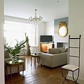 Möbelstilmix im Wohnraum mit zierlichem Eisenstuhl und Beistellstischen im Rokokostil neben modernen Polstersofas