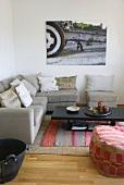 Corner sofa and comfortable pouffe next to dark wood coffee table