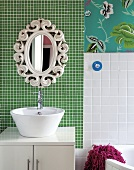 White wash basin on base unit and retro mirror on wall with green mosaic tiles