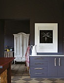 Dark sideboard against partition of same colour with modern artwork on white mount next to open doorway showing view of white farmhouse cupboard in room beyond