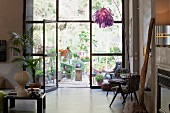 Artistic collection of furniture and objets in loft apartment in front of glass wall with view of greenery on terrace