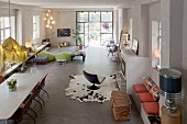 View from gallery into comfortable interior of spacious loft apartment with industrial windows