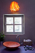 Atmospheric bathroom with ceramic wash basin and warm orange, hanging light over a pastel violet vanity in front of an exposed concrete wall