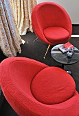 50's look red upholstered chairs and side table on a black carpet in the corner of a room in front of a window with floor to ceiling drapes