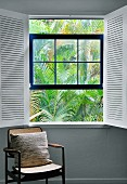 Pillows on an antique chair by a window with open, white interior shutters and a view of palm fronds