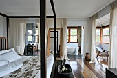 Four-poster double bed with dark wood frame in spacious bedroom and white, floor-length curtains screening ensuite bathroom